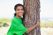 Pretty environmental activist hugging tree on a sunny day in the countryside
