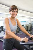 Smiling brunette working out on the cross trainer at the gym