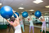Fitness class holding up exercise balls in studio at the gym