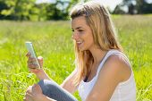 Pretty blonde sitting on grass sending a text on a sunny day in the countryside