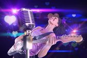 Pretty girl playing guitar against digitally generated cool nightlife design with hearts and stars