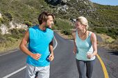 Fit couple running together up a road on a sunny day