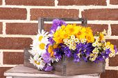 Beautiful flowers in crate on brick wall background