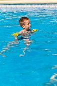 Happy boy swimming with floaties in swimming pool