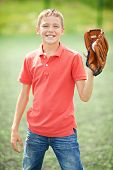 Portrait of active boy with caught baseball looking at camera in the countryside