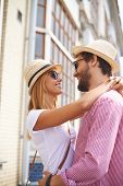 Happy girl and her boyfriend in hats and sunglasses looking at one another with smiles outdoors