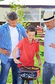 Cute boy frying sausages with his grandfather and father near by