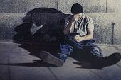 white wasted young man sitting on street against wall feeling miserable and s