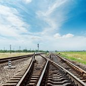 crossing of railroad under blue sky with clouds