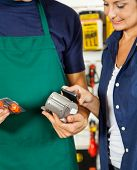 salesman holding electronic reader while female customer making payment through mobilephone in hardware store