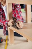 Midsection of female carpenter using planer on wooden shelf at workshop