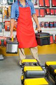 Low section of salesman carrying toolboxes in hardware store