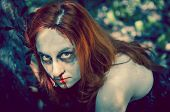 Woman zombie portrait outdoors. Dark lighting. Color was changed to emphasize the atmosphere of horr