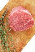 red fresh fillet chops : raw beef fillet on wooden board with thyme ready to prepare . isolated over