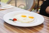 fried eggs with salad on wooden table ready to eat outside cafe