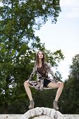Beautiful young woman in colorful dress in summer park