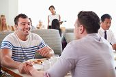Male Couple Enjoying Breakfast In Hotel Restaurant