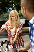 Happy attractive casual blonde woman with bicycle outdoor, smiling, focus in background.