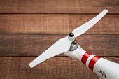 flexible, plastic propeller of a small drone (quadcopter) against red barn wood