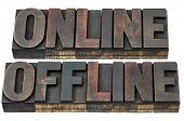 online and offline - internet concept - isolated words in vintage letterpress wood type with ink patina