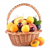 fresh fruits in a basket isolated on white background
