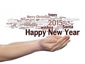 Concept or conceptual Happy New Year 2015 or Christmas abstract holiday text word cloud held in hand isolated on background