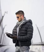Handsome trendy man in winter fashion  looking down at a tablet PC