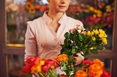 Woman at flower shop holding bunch of flowers