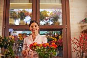 Portrait of a friendly girl at the counter of flower shop