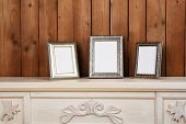 Photo frames on chest of drawers, on wooden wall background