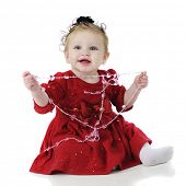 An adorable, dressed-up baby girl happily playing with strands of heart-shaped beads.  On a white background.