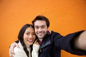 pic of two women taking cell phone  - Close up portrait of a young man and woman smiling while taking selfie - JPG