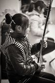 A chinese girl is playing on a traditional music instrument