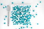 Large Pile Of Teal Colored Pills On White Plate Topview