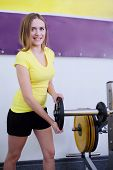 young girl puts the disks on the barbell