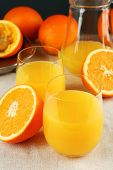 Glass of orange juice with slices on tablecloth background