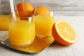 Glass of orange juice with slices on metal tray on table with tablecloth and color wooden wall background