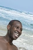 Smiling man near the raging Atlantic Ocean, Malika beach, Senegal,
