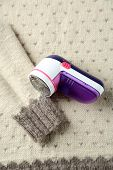 picture of lint  - Wool shaver on wool sweater background - JPG