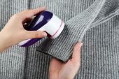 stock photo of lint  - Female hands with Wool shaver on wool sweater background - JPG