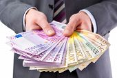 pic of bribery  - Businessman holding many euros banknotes - JPG