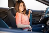 stock photo of seatbelt  - Gorgeous young Latin woman putting her seatbelt on before driving her car