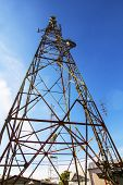 stock photo of antenna  - Telecommunication mast with microwave link and TV transmitter antennas over a blue sky - JPG