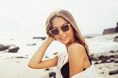 stock photo of sunny beach  - Outdoor summer beach tropic portrait of young sexy sensual tanned sport woman in sunglasses posing on the sea in sunny weather and have fun in vacation time - JPG