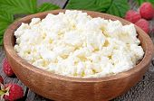 stock photo of curd  - Fresh curd cheese in wooden bowl close up view - JPG