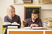 picture of tutor  - Schoolboy makes engaged homework with the tutor - JPG