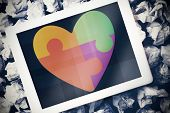 foto of autism  - Autism awareness heart against tablet pc with blue screen - JPG