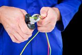 pic of pliers  - Electrician cutting wire with pliers against black - JPG
