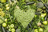 pic of green bean  - Heart made of green beans over green fruit and vegetable background - JPG