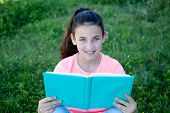 foto of  preteen girls  - Beautiful preteen girl with blue eyes reading a book sitting on the grass - JPG